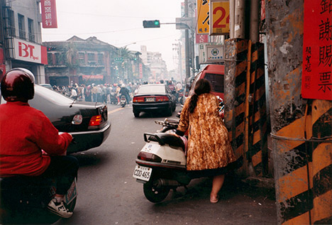 street scene, woman leaning against a motorscooter