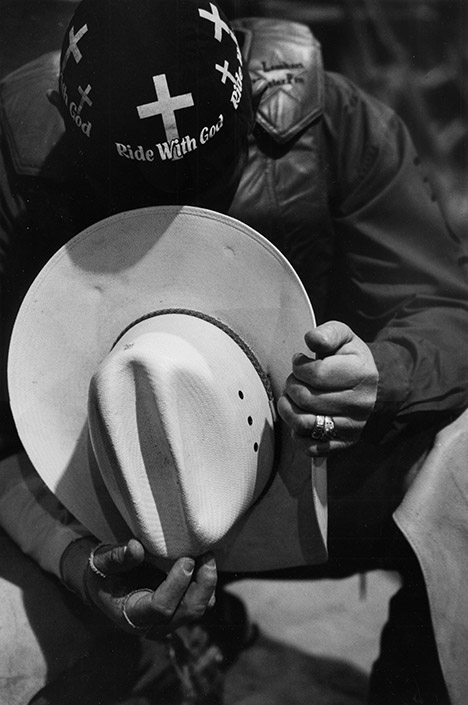 a cowboy holding his hat in front of him and praying