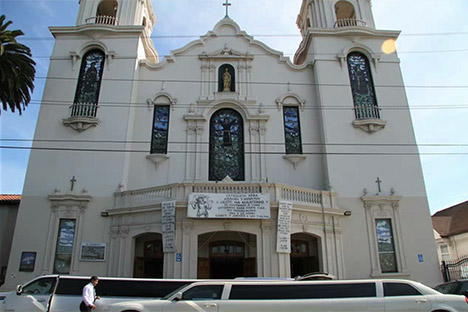 Church facade with two stretch limousines parked in front