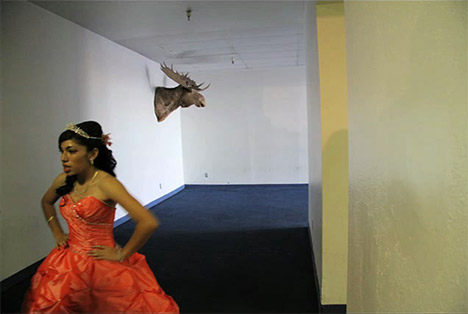 Young woman in hallway with moose head on wall
