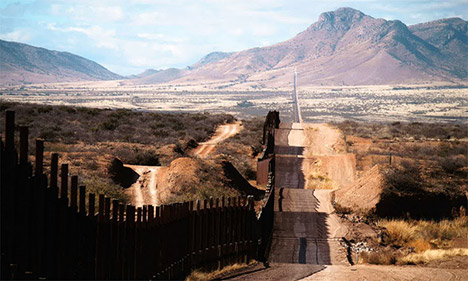 Border wall and road with mountains in distance