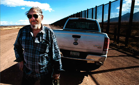 Man with pickup truck next to border wall