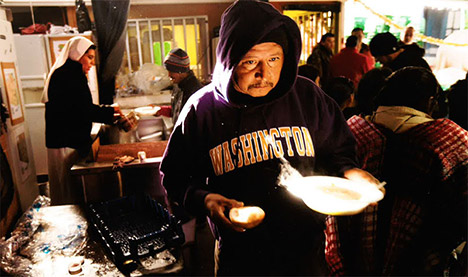 Man with hooded sweatshirt holding plate of food