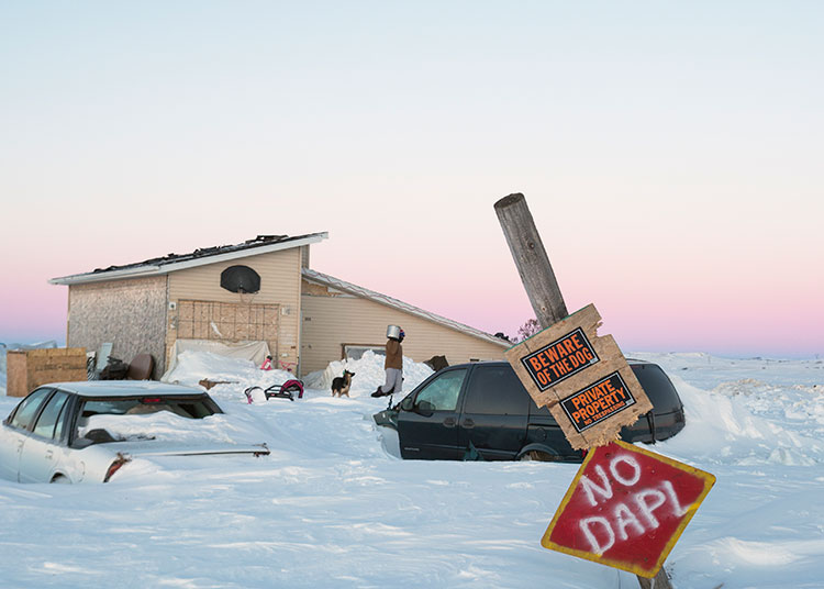 House and vehicles buried in snow and a sign in the foreground that warns 'Beware of Dog', 'Private Property', and 'No DAPL'.