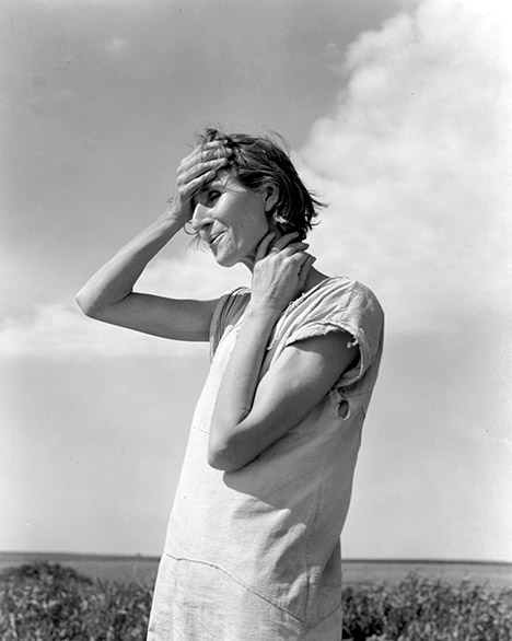 Dorothea Lange photo of a woman in light dress with hands on forehead and neck